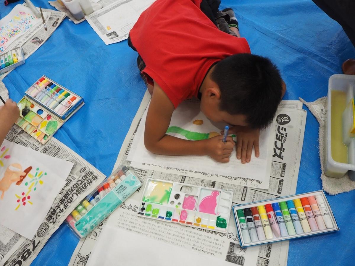 2018年8月出張の小学校連携企画にて、竹灯篭を飾る絵を描いている小学生